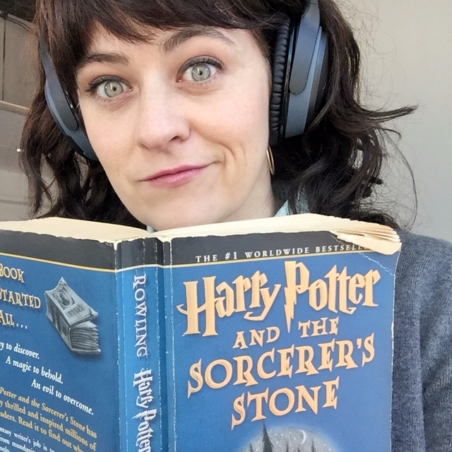 girl reading harry potter with headphones