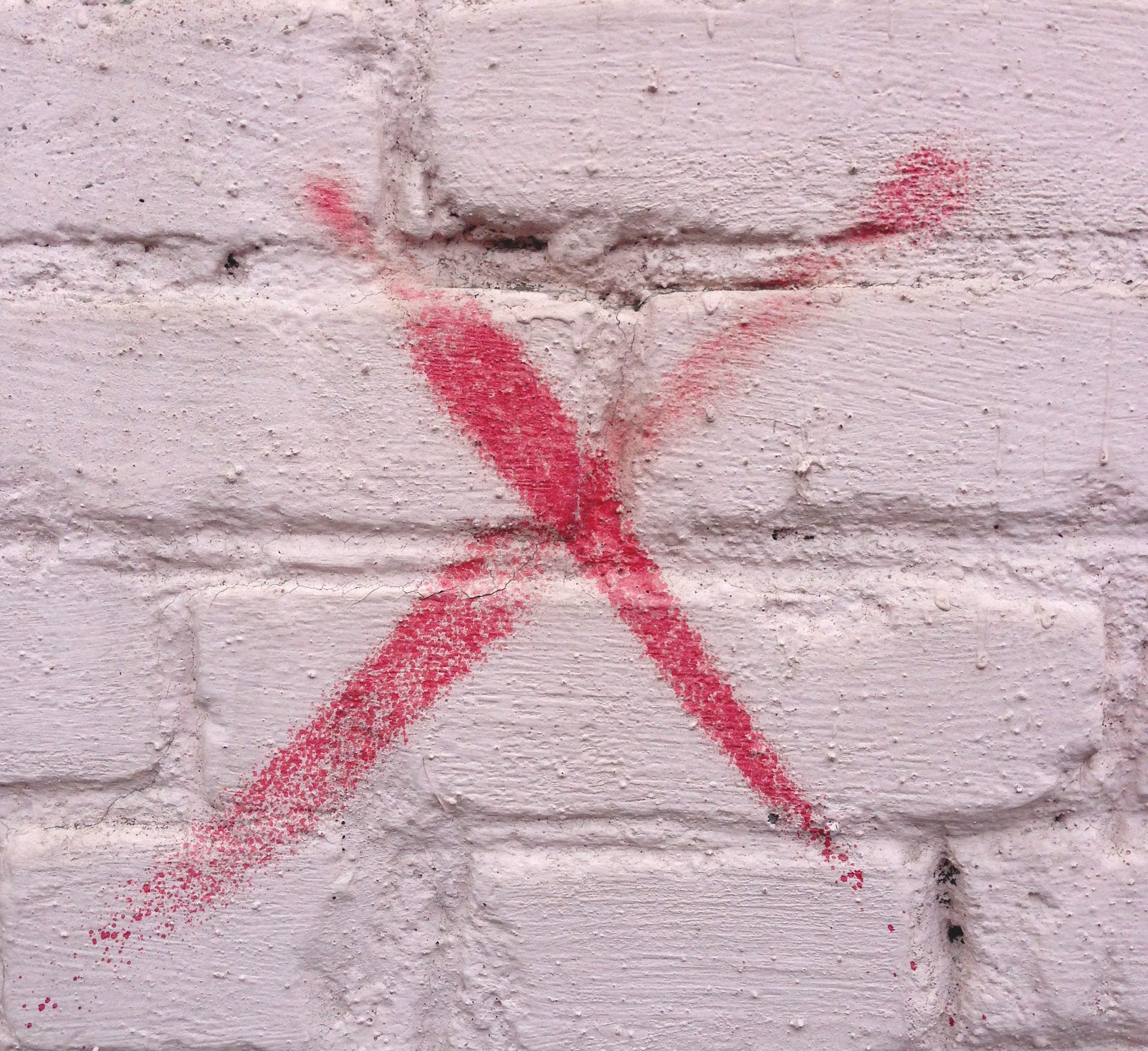 x painted on a brick wall