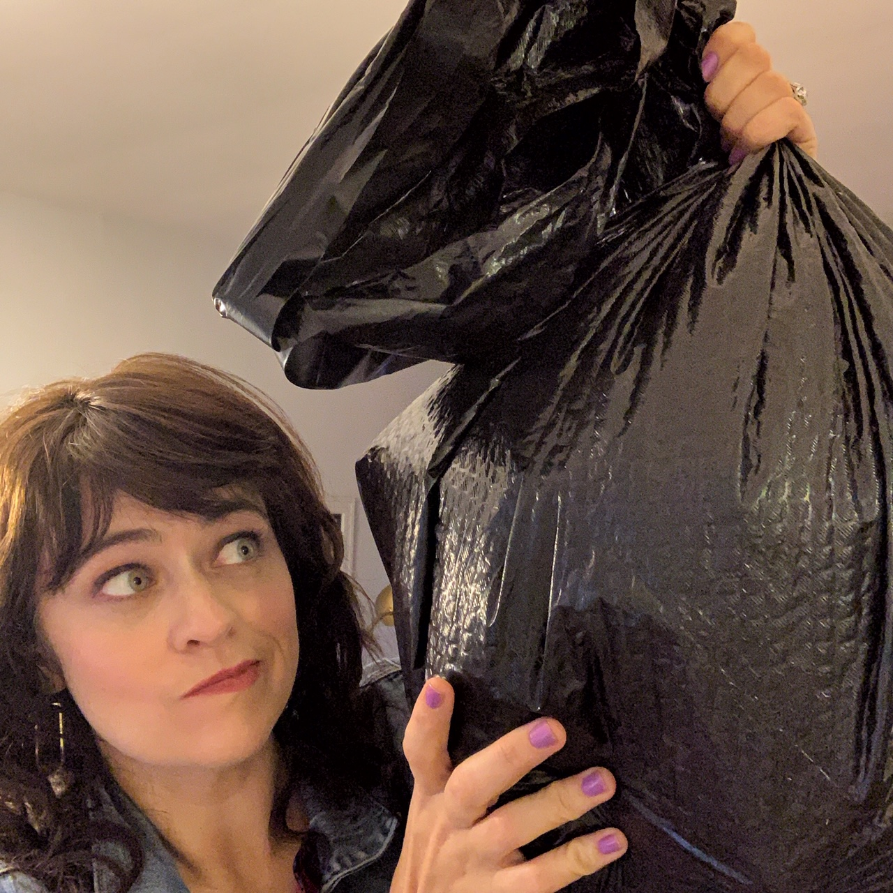 girl holding trash bag