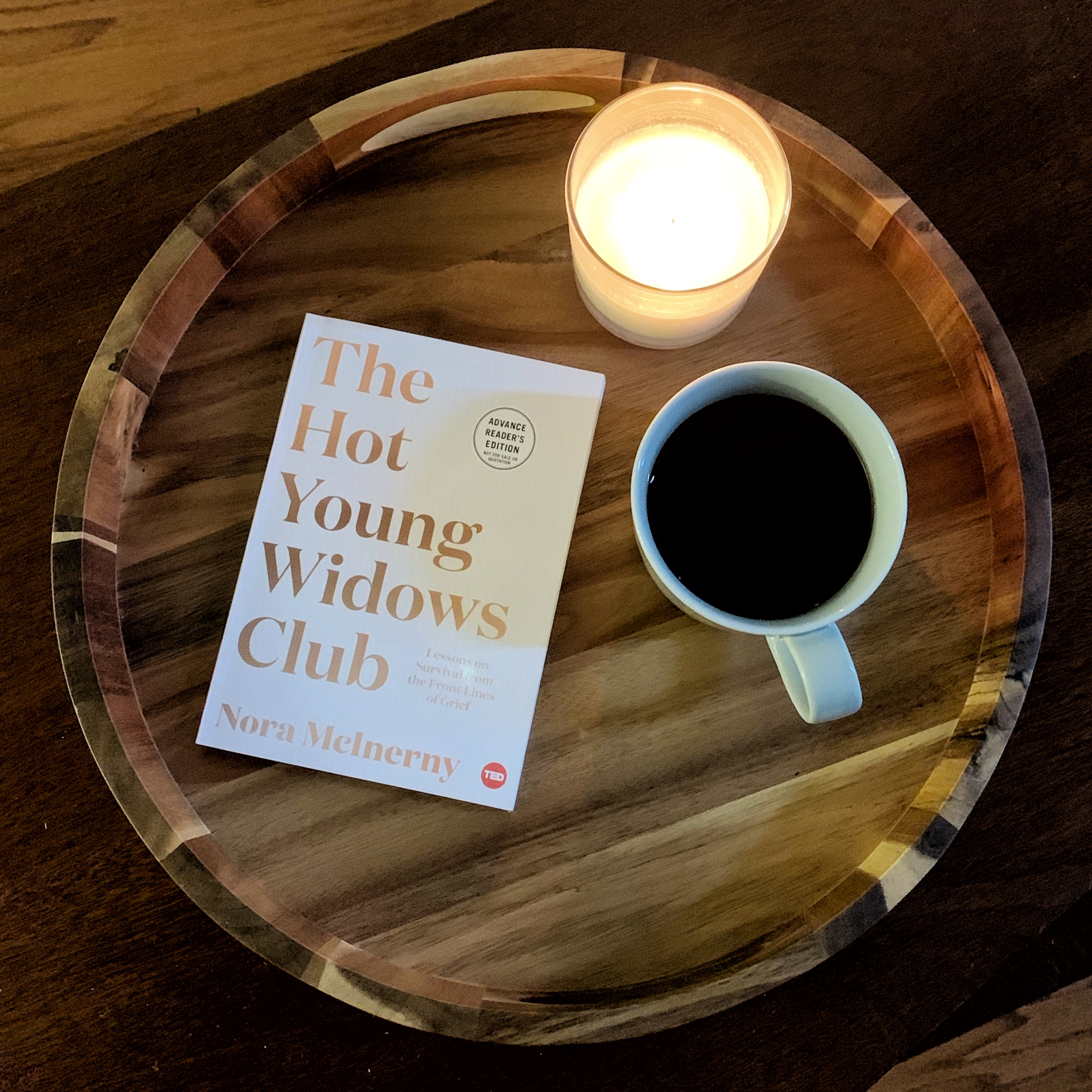 copy of hot young widows club book with a candle and a coffee sitting on a tray