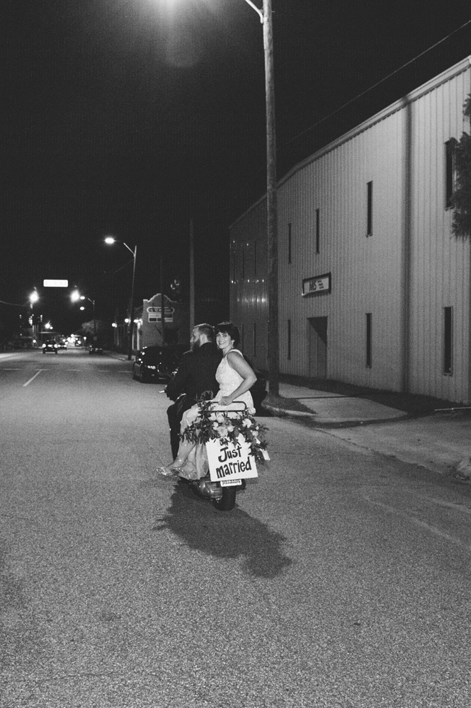 bride and groom leave wedding on vespa