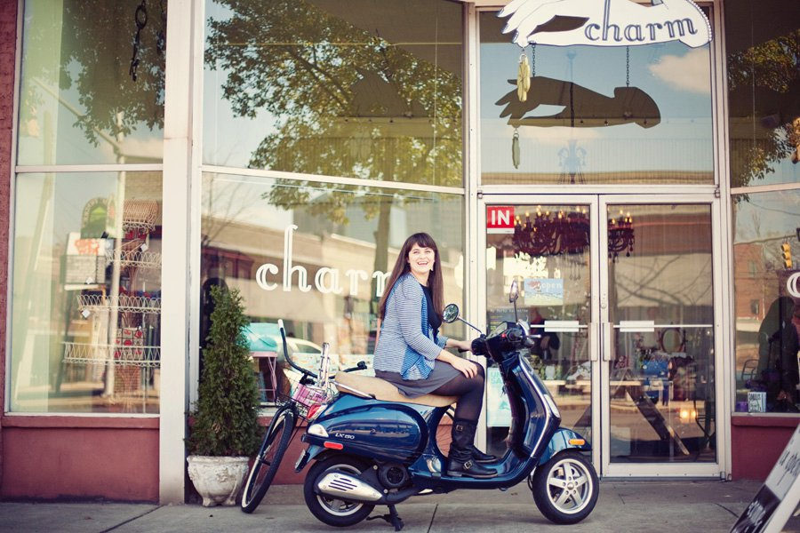 carrie rollwagen sitting on a scooter in front of the jewelry store charm