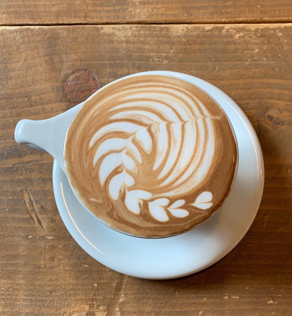 coffee art in a cappuccino on a wooden table